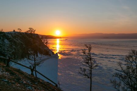 Sunset scene at cape of Burkhan with frozen ice Lake Landscape and sunset scene at cape of Burkhan in winter with background of frozen Lake Baikal; in Siberia, Russian Federation. 写真素材