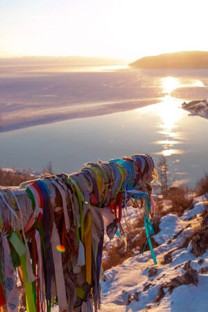 Headwaters of Lake Baikal in evening sunset light; view from high observation spot in winter season; foreground is shaman wood with many colourful cloth stripes tied.