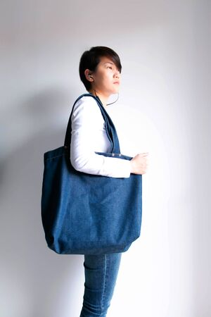 Side view of woman in white long-sleeve T-shirt and jeans with earphone in ears; carry denim shopping tote bag on the shoulder; concept of recycle and save the earth.