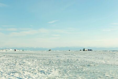 Scene of Lake Baikal landscape in winter in february; with many tourists and local people walk and drive or doing leisure activities on ice surface that formation from weather under freezing point mak