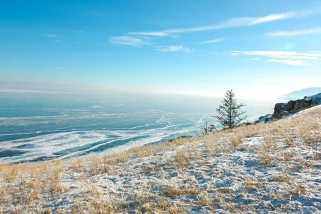 Beautiful scene of Lake Baikal ice surface, boundlessly hills and sky that all in light blue and white color; scenic from view point cape in Olkhon island, Siberia, Russia.