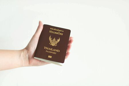 A hand holding the passport of Thailand on white background with copy space.
