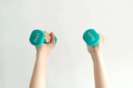 Close-up of two hands of woman lifting pastel-blue dumbbells overhead weighing 1 kilogram in each side; on white background. health care and exercise concept.(soft focus)