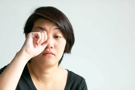 Close-up of woman use hand rubbing her eye with sleepy face. Concept of health care and medical.