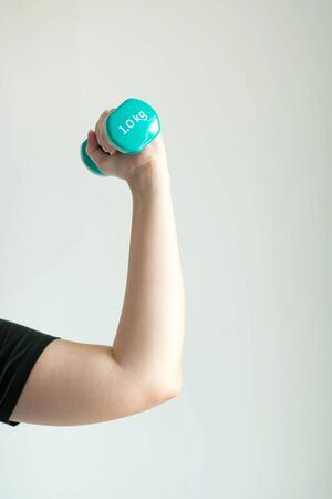 Left hand of woman lifting up pastel-blue dumbbells weighing 1 kilogram in close-up on white background; concept of health care and exercise.