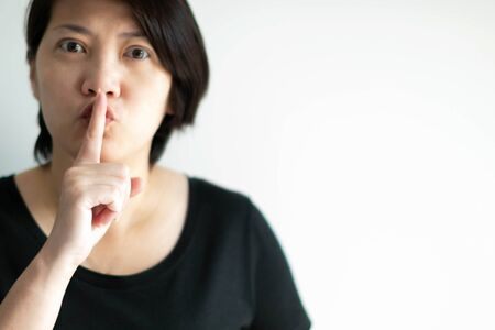 Close-up image of woman use index finger touching on lips in serious face; sending signal telling to keep quiet.