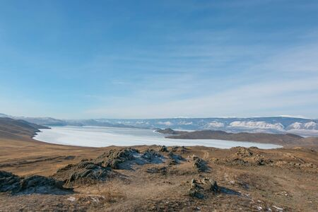 Lake Baikal landscape in winter; beautiful scene created from nature; balance of ground land, ice surface and blue sky.