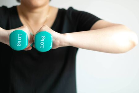 Close-up of woman use two hands lifting pastel-blue dumbbells weighing 1 kilogram in each side; at center of chest on white background. health care and exercise concept.