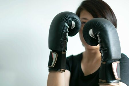 A woman in boxing gloves on fist; in posture of boxing safeguard with an eye catching at the target; on white background with copy space. Concept of determined to success with carefully in business.