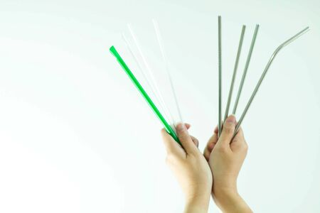 Woman hands hold plastic straws in left hand and stainless steel straws in right hand on white background with copy space; concept of choose for better world; plastic free.