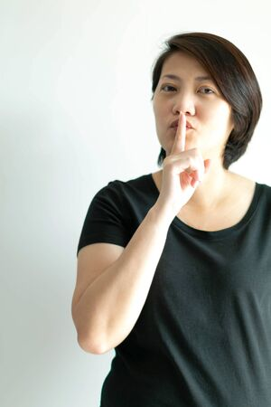 Vertical portrait image of woman use index finger of right hand touching on lips for sending signal telling to keep quiet; or telling to keep secret. 写真素材
