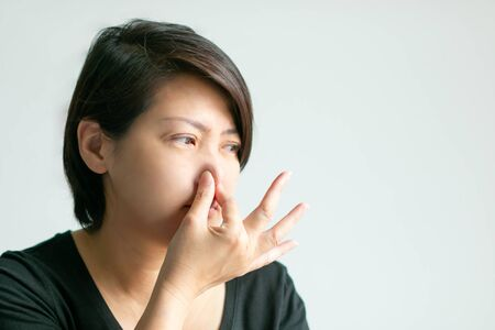 A caucasian woman use thumb and forefinger pinch her nose when scent bad smell; or getting air pollution on white background with copy space. concept of effect from pollution, health care and medical. 写真素材