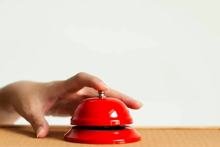 A hand press the red handbell on wooden table on white background; selected focus at the index finger that pressing the bell button. concept of call for assistance with emergency.