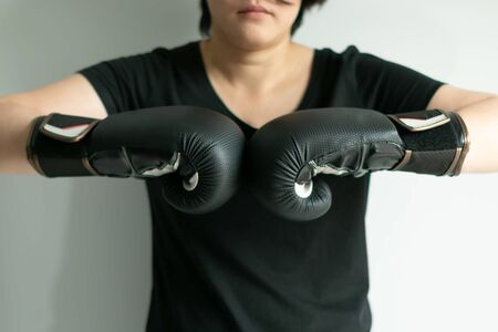 Close-up of woman in a black T-shirt in the posture of hit the black boxing gloves together; the concept of ready for a workout and have good health.