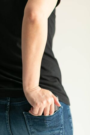 A close-up image in vertical of a woman uses the right hand push blue leather money wallet into the back pocket of jeans after expending money. personal financial and payment concept.