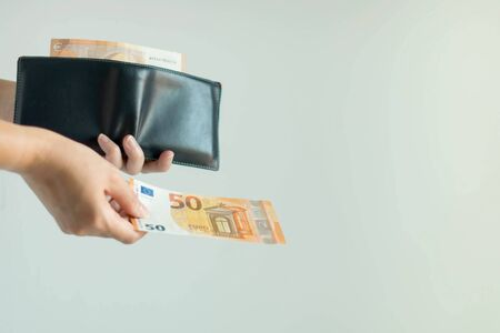 Close-up image of a hand holding a leather short wallet with EURO money in it; and another hand bring forward 50 euro banknote to pay for something on white background with copy space.