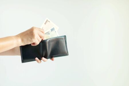 Close-up of hands holding the short wallet and one hand bring out Japan money; in the currency of Yen or JPY; from the wallet to pay for something on white background with copy space. Stockfoto