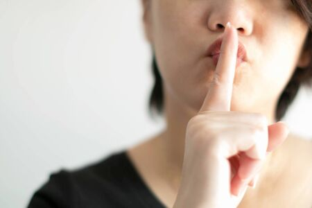 Close-up image of woman use index finger of the right hand touching on lips for sending a signal telling to keep quiet; or telling to keep secret. (soft focus) 写真素材