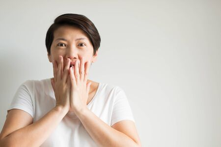 Portrait of a woman uses two hands closing her mouth and looking at the front of her with feeling excited, amazed and happy. Stockfoto