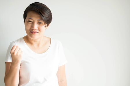 Portrait of a caucasian woman raising her fist and the face expressed the glad for her success; the concept of opportunity and success in business. Stockfoto