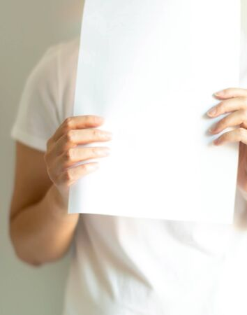 Close-up of a woman in a white T-shirt holding blank white paper; for fill a message or an advertise sentence. concept of communication and marketing.