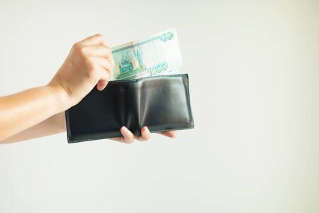 Close-up of hands holding a short wallet and one hand bring out the money in the currency of Rouble or RUB; from the wallet to pay for something on white background.