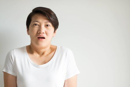 A woman portrait in an expression of stunned; eyes and mouth opened from a shocked reaction; on white background with copy space.