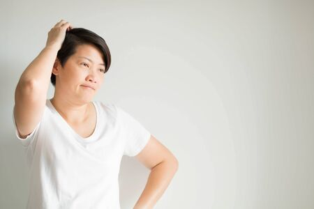 A portrait of an Asian woman in funny reaction with a problem her meet; look puzzled, confused and fed up; sighing and scratching head on white background with copy space.