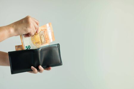 Close-up of a hand holding a short wallet and another hand bring out the money from the wallet in the currency of EURO or EUR for spend to buy something in countries in European Union on white background with copy space. Stockfoto