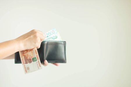 Hand holding a wallet and Russian money in RUB currency; another hand-selecting more banknotes from the wallet prepare for spending on white background with copy space, select focus at the right hand.