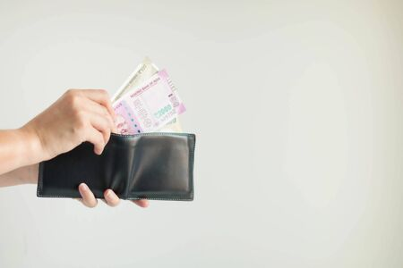 Close-up of hands holding a short wallet and one hand bring out the money in the currency of Rupee or INR; from the wallet to pay for something on white background.