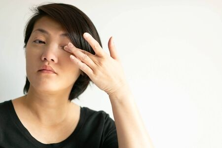 Portrait of an Asian woman that itch her eye and rub it with a finger; that one of forbiddance for the contagious disease situation. concept of healthcare and medical.