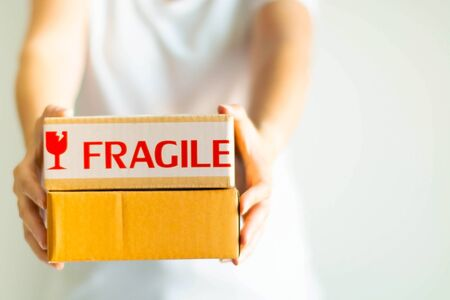 Close-up image of a person standing and deliver two parcel boxes that one of the parcels has the fragile warning symbol on white background; selective focus at the parcels and blurred others detail.