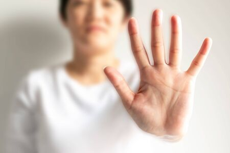 A woman raises an arm and showing a palm with five fingers; it is hand signs or the body language in the meaning of please stop; say no; or forbid, on a white background and selected focus only at the palm. Stockfoto