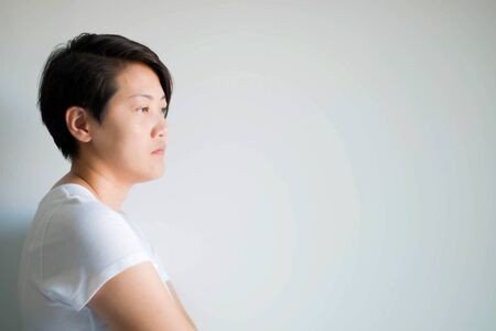 A side portrait of an Asian woman is distraught standing and introspective, unhappy expression and feeling negative. The concept of a depression patient, that in the medical caused by brains.