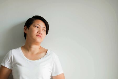An Asian woman portrait is standing lean against the wall in a depressed mood; think over; and confused on white background with copy space.