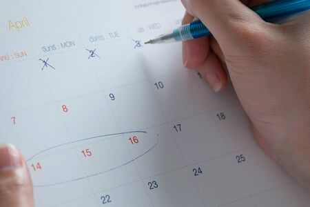 Close-up of a hand holding a pen cross out at date in April in Thai calendar, for counting down to planned traveling at day-off in Songkran festival. (in Thai calendar have the Thai language that meaning the day in a week)
