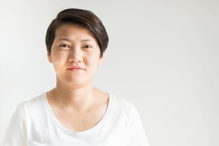 A forty ages Asian woman portrait is smiling; with her real skin face that has freckles, wrinkles and furrow; no makeup on white background with copy space.