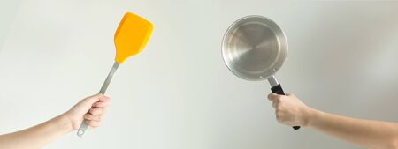 Hands of two persons that holding the spatula against the pot ready for cooking; a symbol of chef and meal; concept of fry and stir fry that has fat versus the boil and stewed food that low calories.