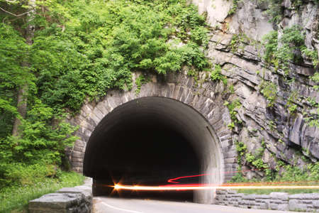 Mountain tunnel with light trails from traffic