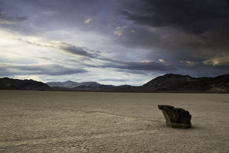Lone rock on a desert playa photo