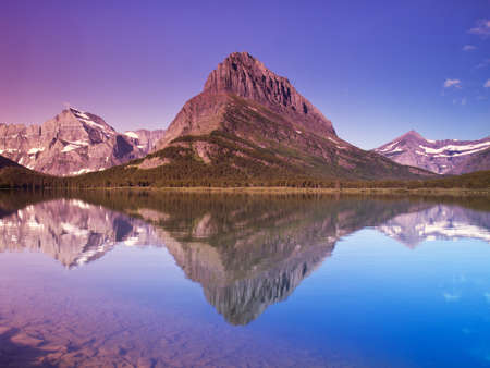 Glacier National Park Reflected in Swiftcurrent Lake Stock Photo