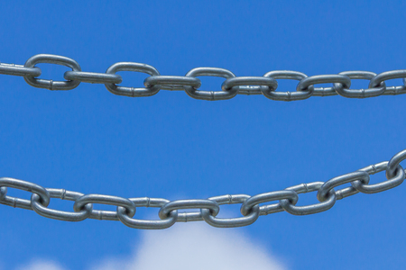 forced perspective: Chains on a blue sky background, link concept