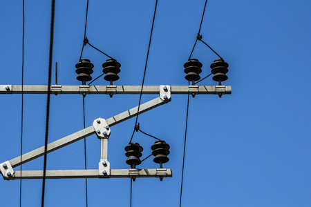 Electric wires with insulators are stretched out on top on a sky background, industrial background
