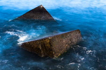 Granite wavebrakers in a Gulf of Riga, Latvia after sunset in August, slow shutter speed