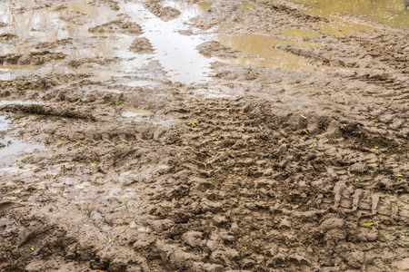 Tire tracks on a wet muddy road, abstract background