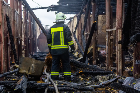 firefighter stands among the ruins of a fully burned farm, disaster scene