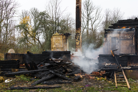 charred wooden parts of a burnt house in Latvia on November