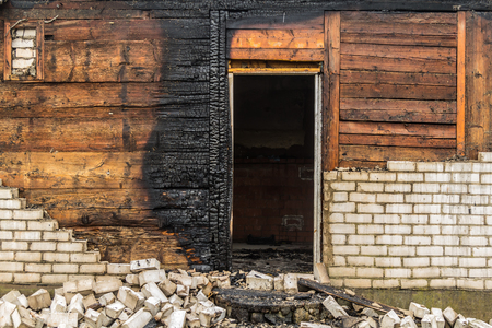charred wooden parts of a burnt house in Latvia Stock Photo