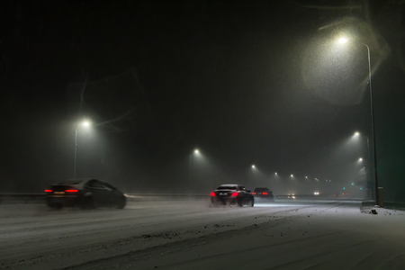 cars driving on the road at night during a snowfall at night Stock Photo
